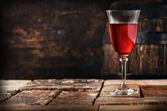 Ett exponeringsglas av rött vin på en gammal lantlig tabell Royaltyfri Fotografi