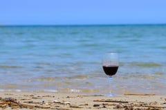 Ett exponeringsglas av rött vin på strandkusten i sommar på solig dag med det blåa havet arkivfoto
