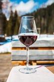 Ett exponeringsglas av r?tt Cabernet vin i en loge i Cortina d'Ampezzo, Dolomites, Italien royaltyfria bilder