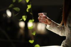 Ett exponeringsglas av ren mineralvatten i h?nder f?r kvinna` s Begrepp av milj?skydd, sund drink royaltyfri foto