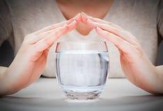 Ett exponeringsglas av ren mineralvatten som täckas av kvinnas händer symbolism för hav för floder för miljöhavskydd Arkivfoton