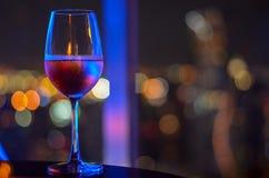 Ett exponeringsglas av rosa vin med bokehljus arkivfoton