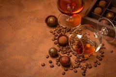 Ett exponeringsglas av stark alkoholdryckkonjak eller konjak och godis av mörk choklad på en brun texturerad bakgrund arkivfoto