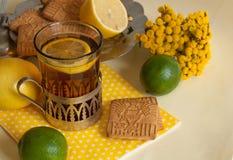 Ett exponeringsglas av svart te i en glass hållare, några kex, mogna citroner och limefrukter på en linne ytbehandlar mot den lju Arkivbild
