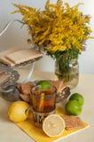 Ett exponeringsglas av svart te i en glass hållare, några kex, mogna citroner och limefrukter på en linne ytbehandlar mot den lju Royaltyfria Bilder