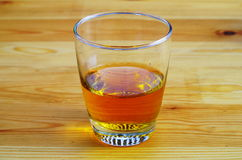 Ett exponeringsglas av te eller whisky på en trätabell Royaltyfri Bild