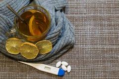Ett exponeringsglas av te med citronen som slås in i en grå halsduk för ull På tabellen ligger en termometer och piller arkivbild