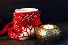 Ett exponeringsglas av te och stearinljuset Arkivbild