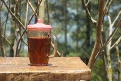 Ett exponeringsglas av te på en trätabell arkivfoton