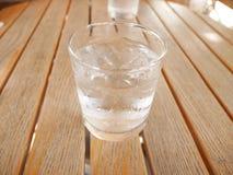 Ett exponeringsglas av vatten med iskuben arkivbilder