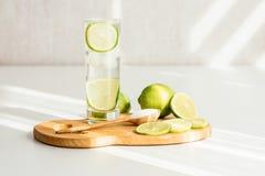 Ett exponeringsglas av vatten med limefrukt på ett träbräde arkivfoto