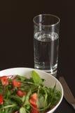Ett exponeringsglas av vatten med ljus tomatsallad i den vita porslinbunken Arkivfoton
