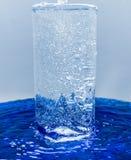 Ett exponeringsglas av vatten, vatten med bubblor flödar över till och med exponeringsglas Royaltyfri Bild