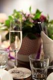 Ett exponeringsglas av vin med bubblor på bakgrunden av blommor Royaltyfri Bild