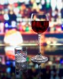 Ett exponeringsglas av vin och ett skott av vodka Royaltyfria Bilder
