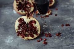 Ett exponeringsglas av vin på en grå bakgrund bland granatäpplen Nära granatäpple och rött granatäpplefrö royaltyfria foton