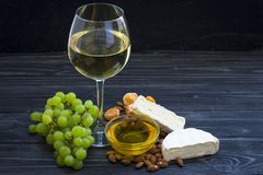 Ett exponeringsglas av vitt vin med ost klipper, fikonträd, muttrar, honung, druvor på en mörk lantlig träbrädebakgrund royaltyfria bilder