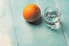 Ett exponeringsglas av vodka med ett orange mellanmål royaltyfria foton