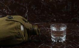 Ett exponeringsglas av vodka på gravstenen, bredvid den militära gröna flaskan royaltyfria bilder