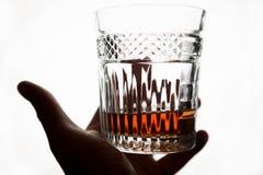 Ett exponeringsglas av whisky eller konjak i hand på vit bakgrund Royaltyfria Bilder