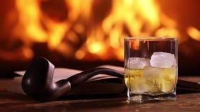 Ett exponeringsglas av whisky, en öppen bok och ett rör på tabellen arkivfilmer