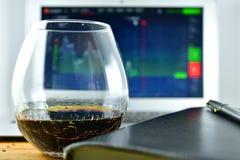 Ett exponeringsglas av whisky framme av en bärbar dator med en materielTicker på t Royaltyfri Foto