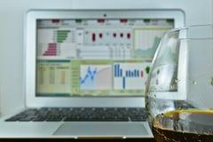 Ett exponeringsglas av whisky framme av en bärbar dator med en materielTicker på t Arkivfoton