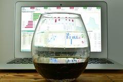 Ett exponeringsglas av whisky framme av en bärbar dator med en materielTicker på t Arkivfoto