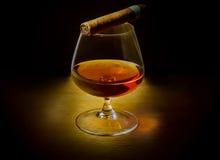 Ett exponeringsglas av whisky med en cigarr royaltyfria bilder