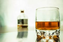 Ett exponeringsglas av whisky med en flaska i bakgrunden Arkivfoto