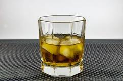 Ett exponeringsglas av whisky och is arkivfoto
