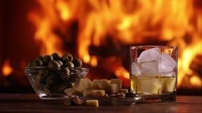 Ett exponeringsglas av whisky och plattan med ost, oliv och muttrar arkivfilmer