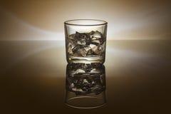 Ett exponeringsglas av whiskyis en mörk romexponeringsglasbakgrund Royaltyfri Bild