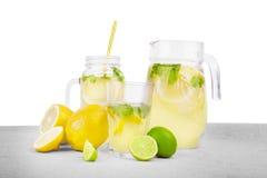 Ett exponeringsglas, en murarekrus och en tillbringare av sommarmojitodrycker från vatten, citroner med den smakliga mintkaramell Arkivfoton