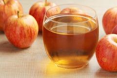 Ett exponeringsglas med äppeljuice och äpplen arkivbilder