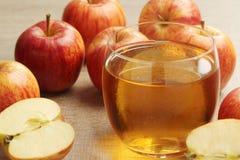 Ett exponeringsglas med äppeljuice och äpplen royaltyfri bild
