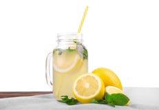 Ett exponeringsglas med en smaklig och användbar coctail från en saftig ljus gul citron och en ny mintkaramell som isoleras på en Royaltyfri Fotografi