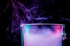 Ett exponeringsglas med färgrik rök royaltyfria foton