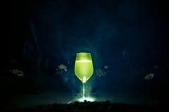 Ett exponeringsglas med limoncello på en mörk bakgrund och rök royaltyfria foton
