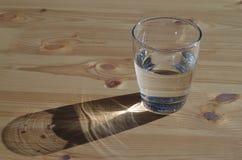 Ett exponeringsglas med vatten på en trätabell Arkivfoto