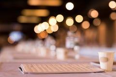 Ett exponeringsglas på tabellen med en anteckningsbok för anmärkningar royaltyfria bilder
