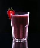 Ett exponeringsglas som är fullt av den saftiga sunda jordgubbecoctailen på en svart bakgrund Halvan jordgubbe med ett blad är öv Royaltyfria Bilder