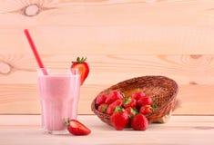 Ett exponeringsglas som är fullt av jordgubbedrinken och en ask med bär på en träbakgrund Jordgubbar i en korg och ett exponering Arkivbild