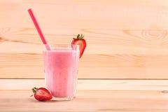 Ett exponeringsglas som fylls med den piskade bärcoctailen En jordgubbesmoothie på en ljus träbakgrund Läckra efterrätter för gou Arkivbild