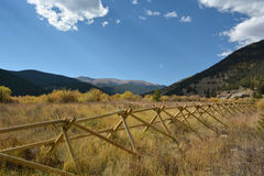 Ett fält i bergen med blåa himlar och ett trästaket Fotografering för Bildbyråer