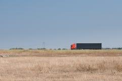 Ett fält och en lastbilbortgång på huvudvägen Royaltyfri Fotografi