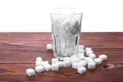 Ett färdigt genomskinligt exponeringsglas av vit raffinerade socker på tabellen, på en vit bakgrund Royaltyfri Bild