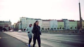 Ett färdigt par som utomhus kör på gatorna av den Prague staden långsam rörelse stock video
