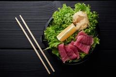 Ett färgrikt uppläggningsfat av sashimien med fisken på plattan med sallad, citronen, wasabi och ingefäran royaltyfria foton