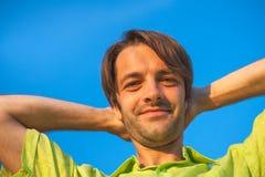 Ett färgståendefoto av en lycklig le haired man för brunett som bär en skjorta för gul gräsplan mot en backround för blå himmel Arkivfoton